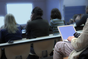 Persone sedute a un meeting navigano usando un sistema Wi-Fi per Fiere