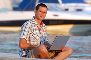 Uomo seduto sulla banchina di un porto naviga tramite Wi-Fi